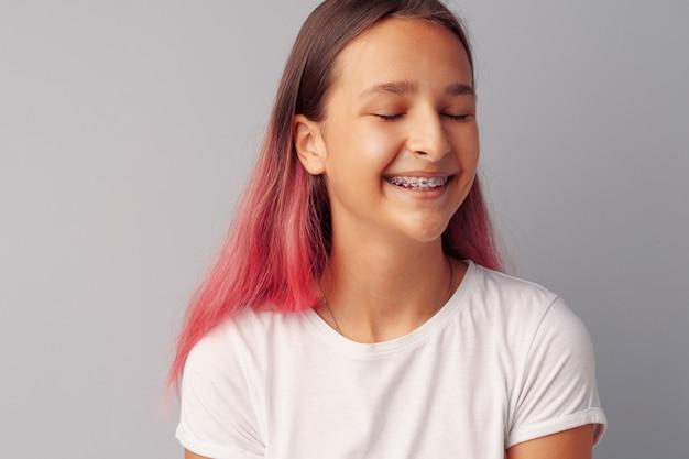 Jonge meisjestiener met roze haar gelukkig en glimlachend over grijze achtergrond