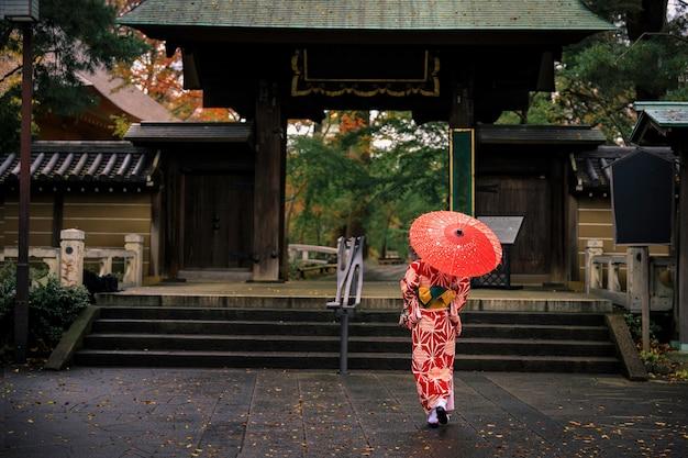 Jonge meisjestoerist die rode kimono en paraplu draagt, maakte een wandeling in de parkingang in de herfstseizoen in japan
