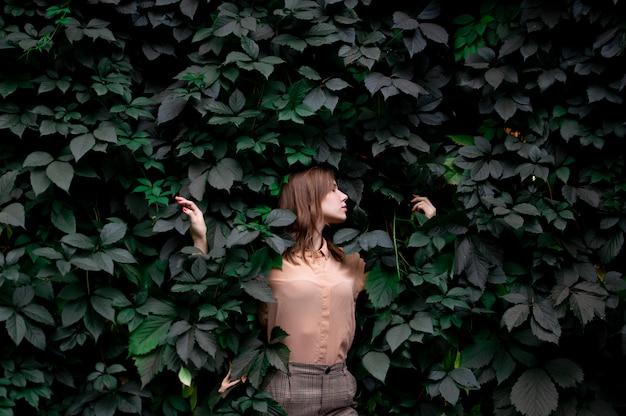 Jonge meisjestribunes in groene bladeren alleen met aard