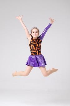 Jonge meisjesturner in een sprong