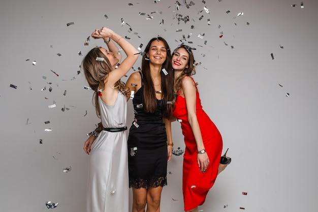 Jonge meisjesvrienden vieren die avondjurken dragen die onder zilveren confetti knuffelen op vakantiepartij op grijze achtergrond