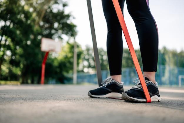Jonge meisjesvrouw die buiten traint en training voor haar handen doet en rubberen elastische banden vasthoudt...