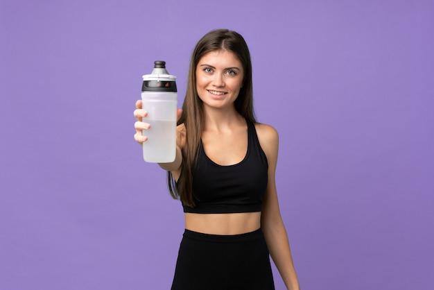 Jonge meisjesvrouw over geïsoleerde achtergrond met de fles van het sportenwater