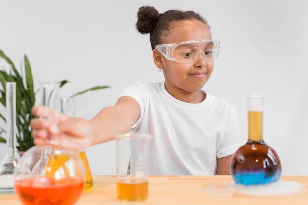 Jonge meisjeswetenschapper die met drankjes experimenteert