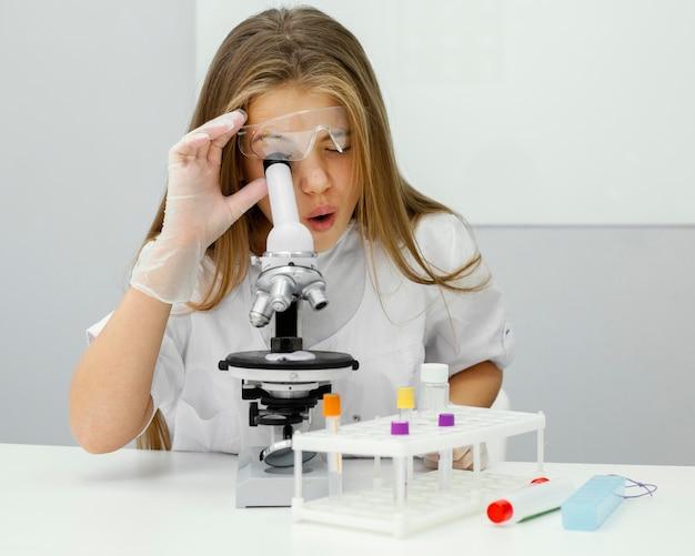 Jonge meisjeswetenschapper die microscoop met behulp van