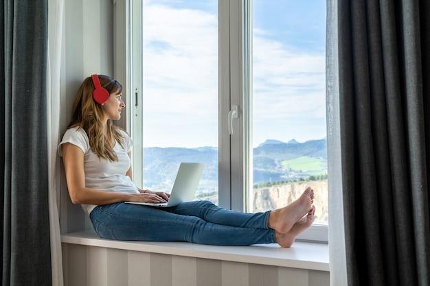 Jonge meisjeszitting in het venster dat aan haar laptop werkt. concept van technologie en studie of werk thuis