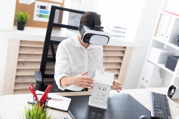 Jonge meisjeszitting in virtuele werkelijkheidsglazen. voor haar op tafel staat de indeling van het huis.