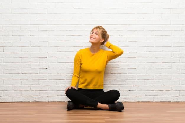Jonge meisjeszitting op de vloer die een idee denken terwijl het krassen van hoofd