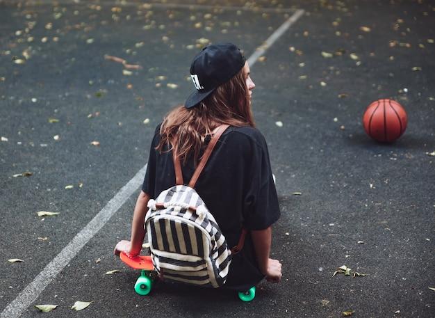 Jonge meisjeszitting op plastic oranje stuiver shortboard op asfalt in glb