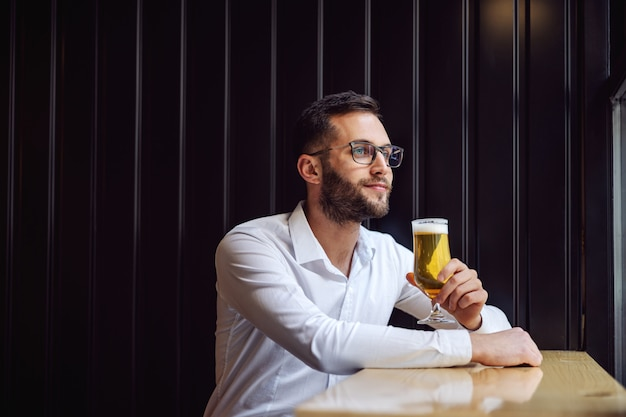 Jonge melancholische zakenman in overhemd zit in de pub naast raam en kijkt er doorheen. hij houdt een glas bier vast.