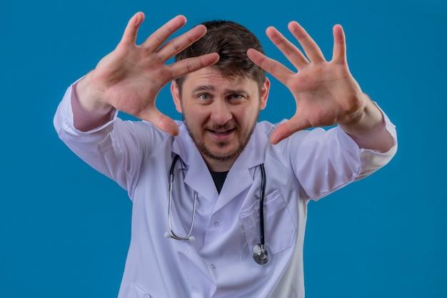 Jonge mens arts witte laag dragen en stethoscoop die aan zijn schone handen tonen en over geïsoleerde blauwe achtergrond glimlachen te camera