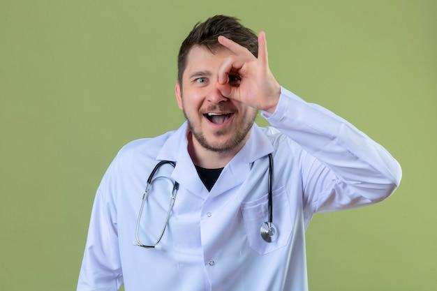 Jonge mens arts witte laag dragen en stethoscoop die ok teken met hand doen en vingers die door teken met grote glimlach over geïsoleerde groene achtergrond kijken