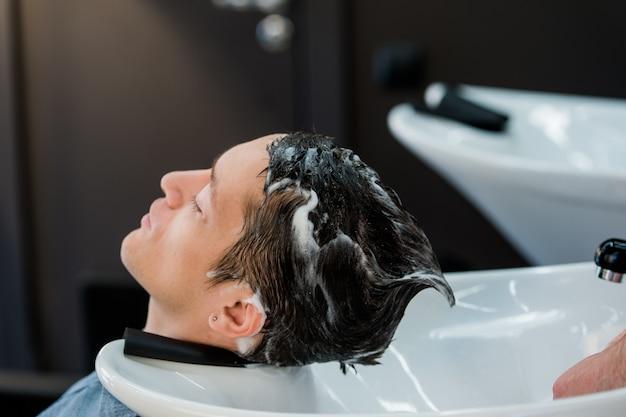 Jonge mens bij kapsalon die zijn haar gewassen krijgt