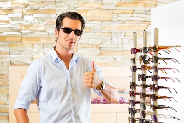 Jonge mens bij opticien het kopen zonglazen