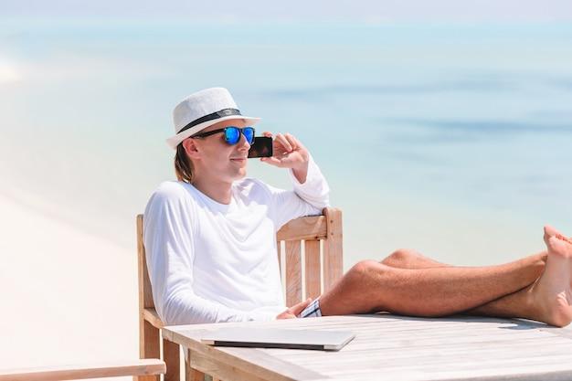 Jonge mens bij tropisch strand dichtbij watervilla