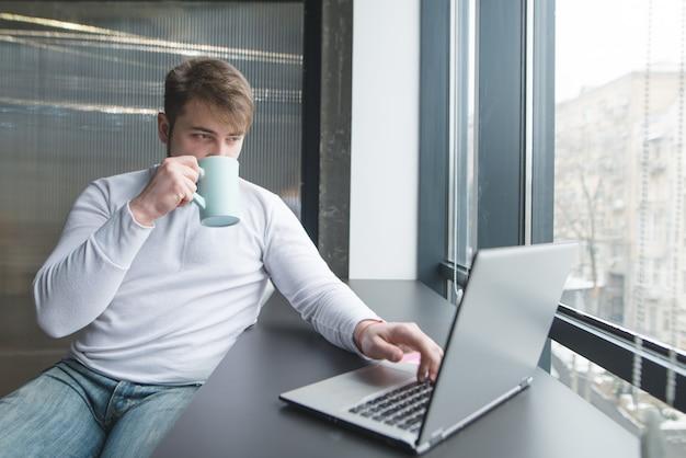 Jonge mens die aan laptop in het coworking werken en koffie drinken.