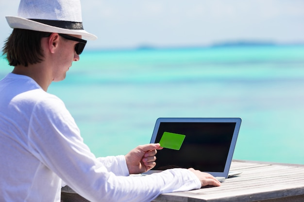 Jonge mens die aan laptop met creditcard bij tropisch strand werkt