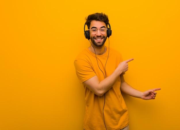 Jonge mens die aan muziek luistert die aan de kant met vinger richt
