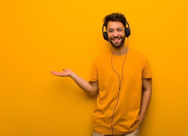 Jonge mens die aan muziek luistert die iets met hand houdt