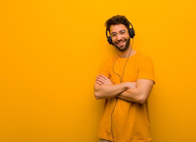 Jonge mens die aan muziek luistert die wapens kruist, glimlachend en ontspannen