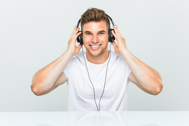 Jonge mens die aan muziek met gelukkige, glimlachende en vrolijke hoofdtelefoons luistert.