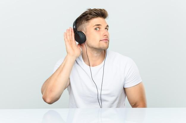 Jonge mens die aan muziek met hoofdtelefoons luistert die een roddel probeert te luisteren.