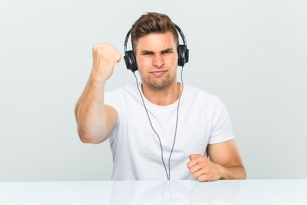 Jonge mens die aan muziek met hoofdtelefoons luistert die vuist tonen aan camera, agressieve gelaatsuitdrukking.
