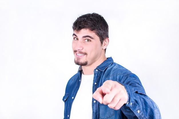 Jonge mens die bij de camera geïsoleerde exemplaarruimte glimlacht