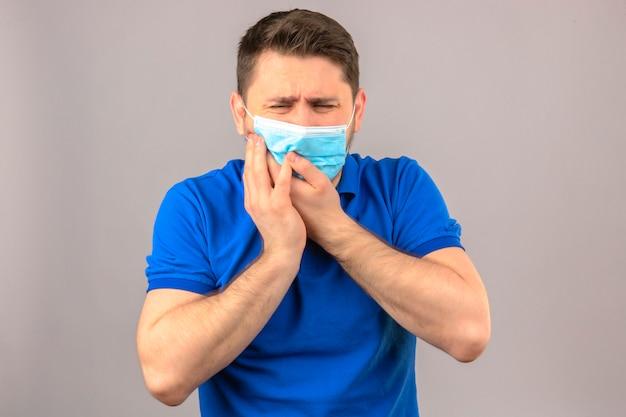 Jonge mens die blauw poloshirt in medisch beschermend masker draagt dat onwel wat betreft wang die aan tandpijn over geïsoleerde witte muur kijkt kijkt
