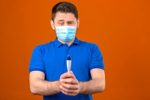 Jonge mens die blauw poloshirt in medisch beschermend masker draagt dat ter beschikking zenuwachtige en ongerust gemaakte digitale thermometer over geïsoleerde oranje muur bekijkt