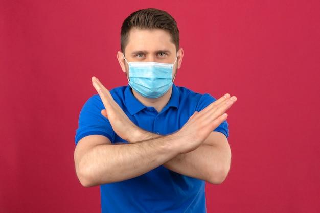 Jonge mens die blauw poloshirt in medisch beschermend masker draagt dat zich met gekruiste wapens bevindt die eindegebaar met fronsend gezicht over geïsoleerde roze muur maakt