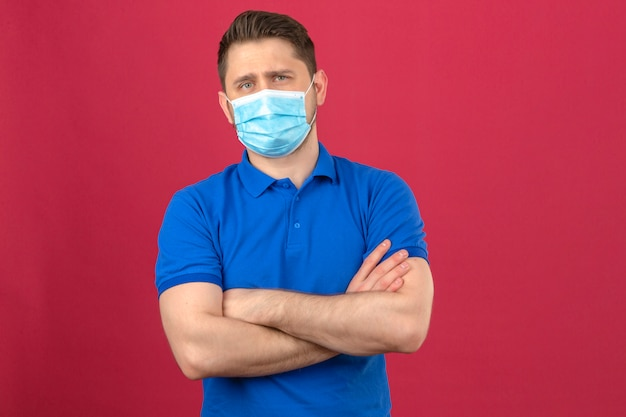 Jonge mens die blauw poloshirt in medisch beschermend masker draagt dat zich met wapens bevindt die met zekere blik over geïsoleerde roze muur worden gekruist
