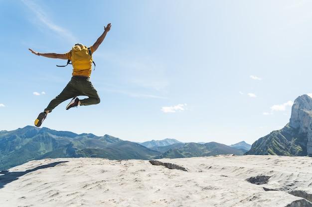 Jonge mens die bovenop een berg springt die gele rugzak draagt.