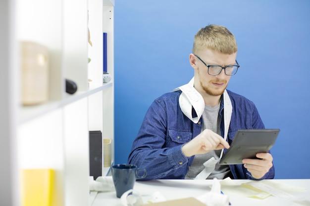 Jonge mens die calculator en cheque van aankoop gebruiken die alleen binnenlandse begroting beheren