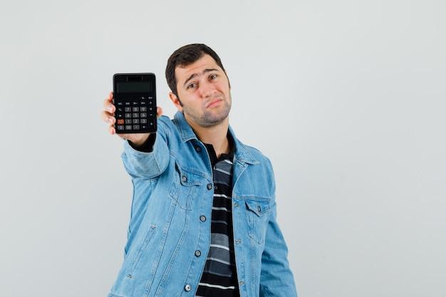 Jonge mens die calculator in t-shirt, jasje toont en wanhopig, vooraanzicht kijkt.