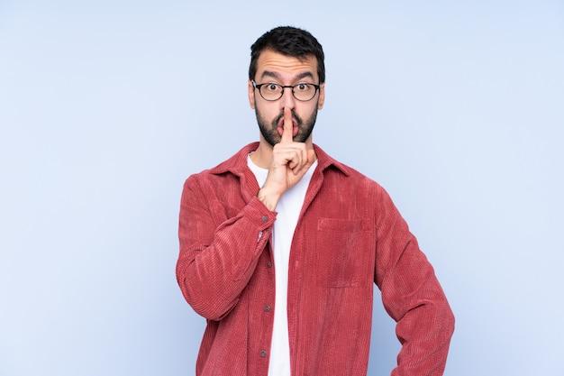 Jonge mens die corduroy jasje over blauwe muur draagt die een teken van stiltegebaar toont dat vinger in mond zet
