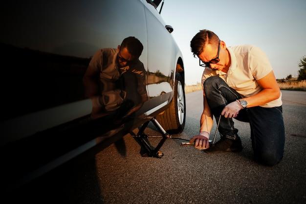 Jonge mens die de auto opheft met