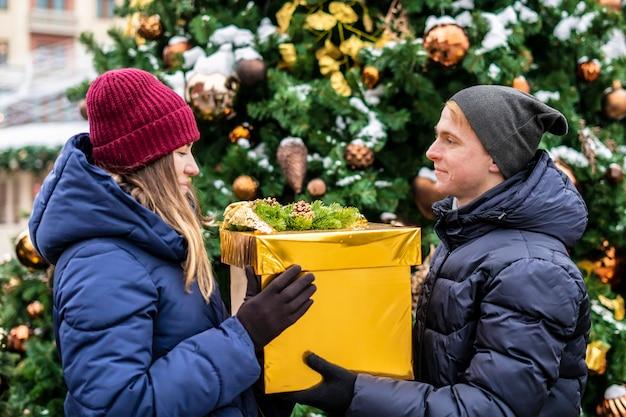 Jonge mens die de doos van kerstmisgit in openlucht geven aan zijn vriendin dichtbij pijnboomboom