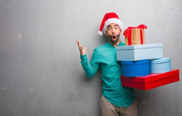 Jonge mens die de giften draagt die van de santahoed giften vieren die een overwinning of een succes vieren