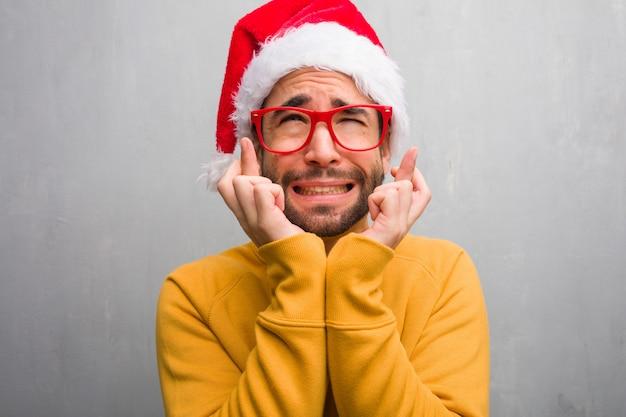 Jonge mens die de holdingsgiften vieren die van de kerstmisdag vingers kruisen voor het hebben van geluk