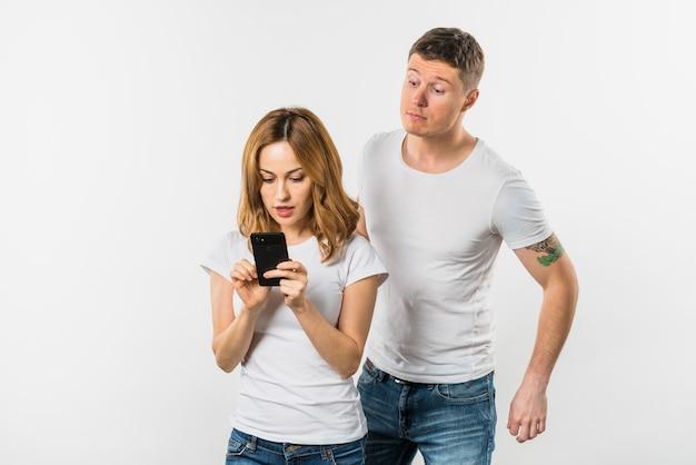 Jonge mens die de mobiele telefoon van een meisje probeert te bespioneren die op witte achtergrond wordt geïsoleerd