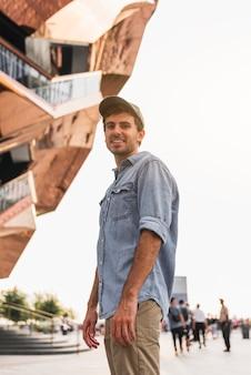 Jonge mens die dichtbij een lang gebouw glimlacht