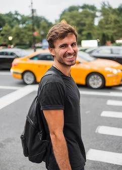 Jonge mens die dichtbij voetgangersoversteekplaats glimlacht
