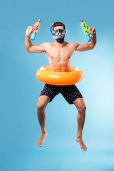 Jonge mens die dragend zwemmende cirkel en glazen springt