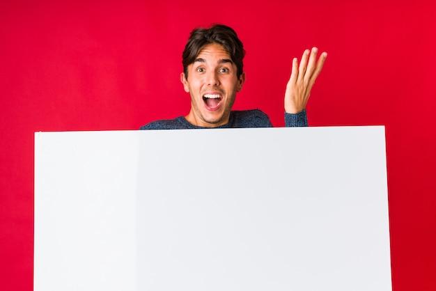 Jonge mens die een aanplakbiljet houdt dat een overwinning of een succes viert