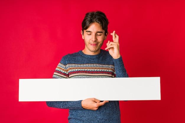 Jonge mens die een aanplakbiljet houdt dat vingers kruist voor het hebben van geluk