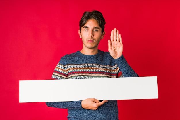 Jonge mens die een aanplakbiljet houdt die zich met uitgestrekte hand bevindt die eindeteken toont, dat u verhindert.