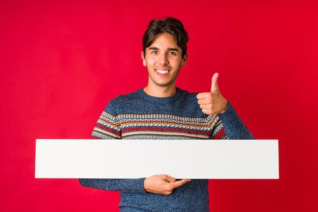 Jonge mens die een aanplakbiljet houdt glimlachend en duim opheft