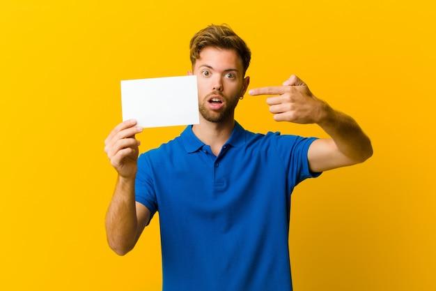 Jonge mens die een aanplakbiljet houdt tegen oranje achtergrond