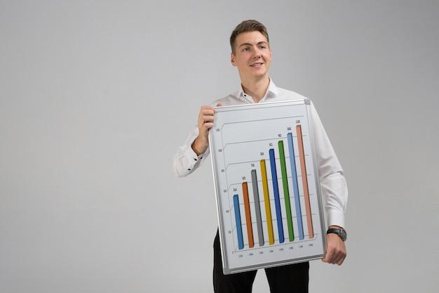 Jonge mens die een affiche met statistieken houdt die op een licht worden geïsoleerd